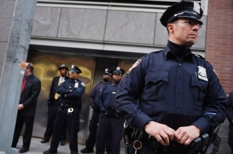 NEW YORK, NY - NOVEMBER 28: Police stand guard as demonstrators, joined by members of the Occupied Wall Street Movment, march near Baruch College in Manhattan to protest against proposed tuition increases over the next few years at the state the school system  on November 28, 2011 in New York City. A heavy police prence met the protesters as city University of New York trustees prepared to vote Monday afternoon on a series of tuition increases at the school.  (Photo by Spencer Platt/Getty Images)