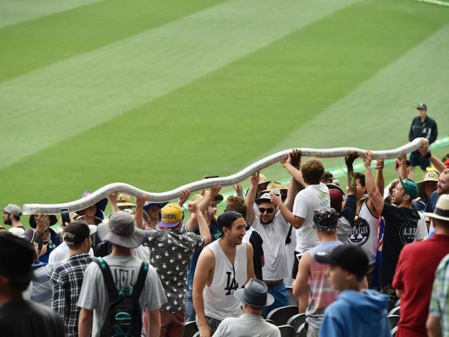 A rowdy section of the crowd gets a beer cup snake going as wet weather halts play. Picture: Jason Edwards
